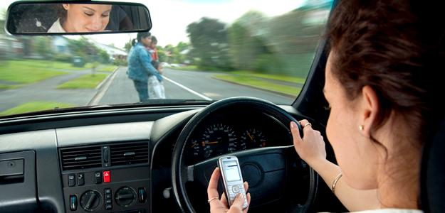 Texting while driving, family crossing road visible in windscreen