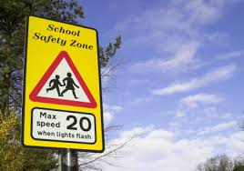 Traffic sign warning of school safety zone where 20mph applies when lights are flashing